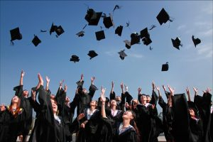 A group of graduates throws their caps in the air.