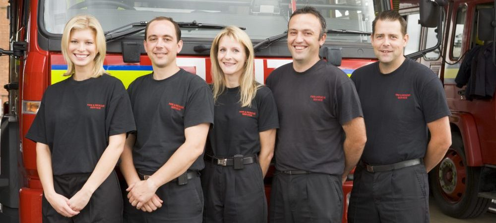 Five firefighters standing in front of a fire truck.