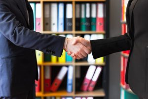 Two people wearing suits shaking hands.