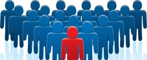 Cartoon representation of a red person standing in front of a crowd of blue people.