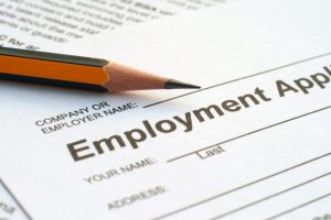 The corner of an employment application is shown next to a pencil.