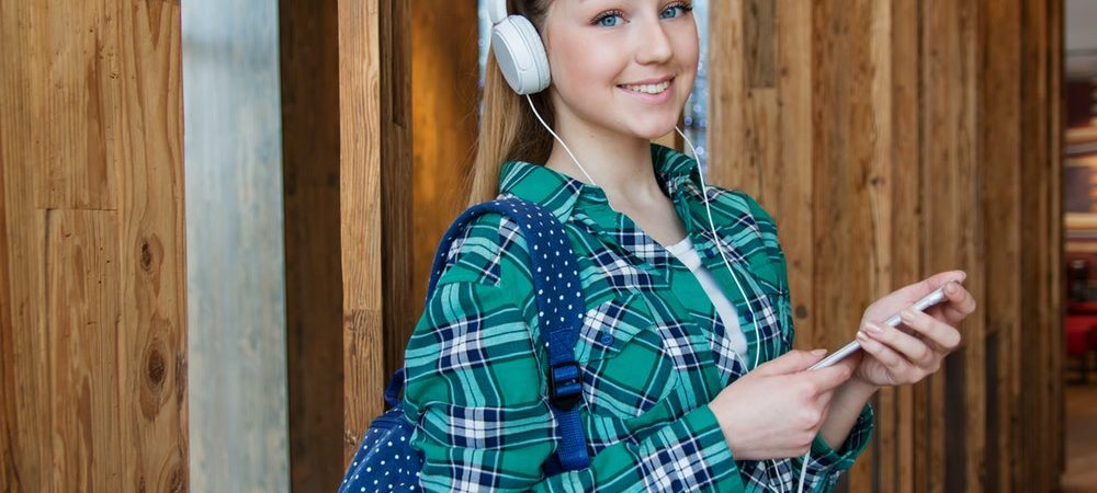 A smiling girl wearing a backpack and headphones stands holding her phone.