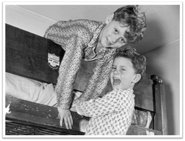 An old-style family photograph depicts two brothers playing on the end of a bunk bed.