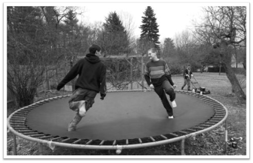 A black-and-white photograph depicts two brothers on a trampoline.