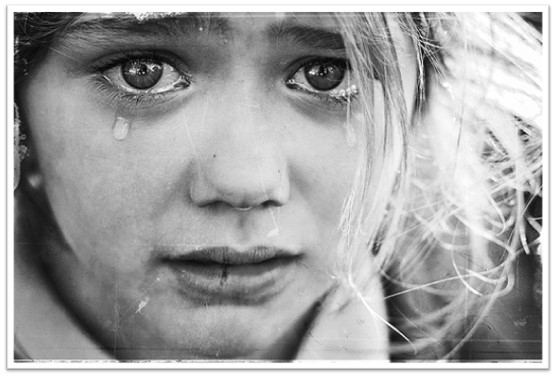 A black-and-white close-up image shows a child's face stained with tears.