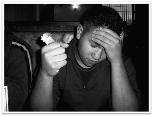 A black-and-white photo depicts a teen with his head in his hands, looking embarrassed.