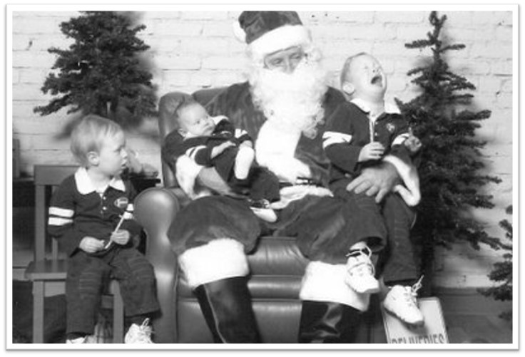 A black-and-white photo depicts three children with Santa Claus; one is scraming and the other two are looking on, displeased.
