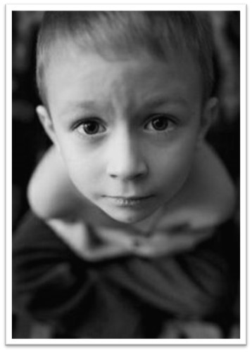 A black-and-white photo depicts the face of a young child who appears to be frightened or scared.