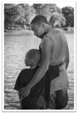 A black-and-white photo depicts an older boy with his arm around a younger boy. The two are seen from the back, overlooking a lake.