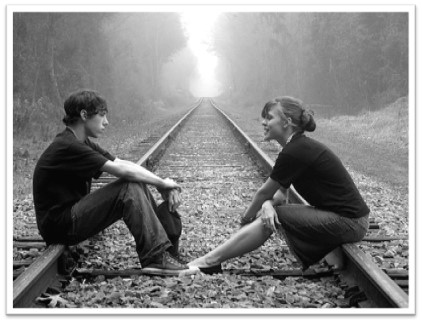 A black-and-white photo shows a teen boy and a teen girl sitting facing each other on a set of railroad tracks.