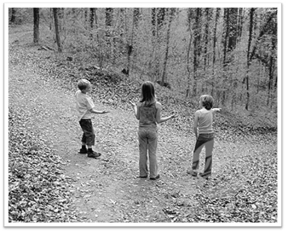 An old-style photograph shows three children standing at the intersection of a trail in the woods. The children are seen from behind and seem to be trying to decide which way to go.