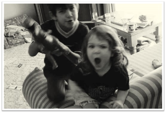 A black-and-white photo blurrily depicts two children fighting over a toy.