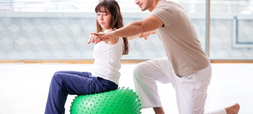 A girl sitting on a medicine ball next to her physical therapist with her arms pointing out.