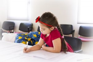 Young girl coloring in notebook.