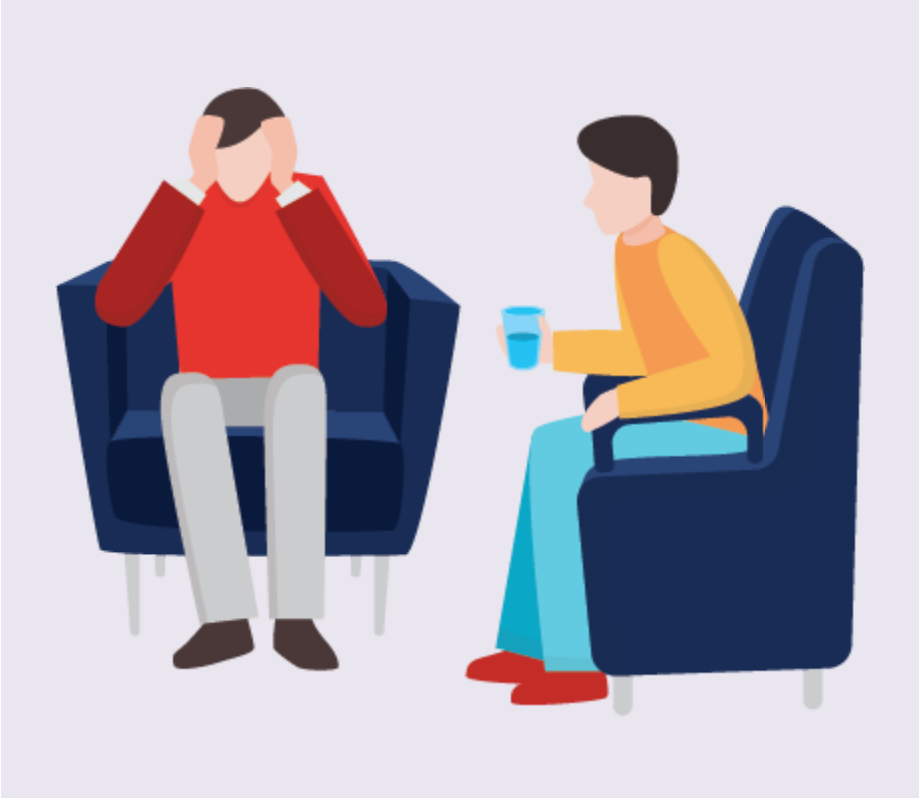 A man with his hands on his forehead sits in a chair next to his therapist.