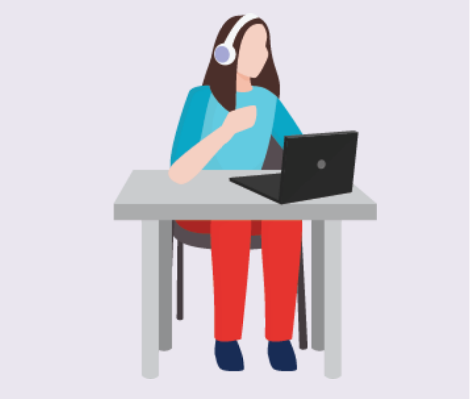 A woman sits at a desk watching a computer while wearing headphones.