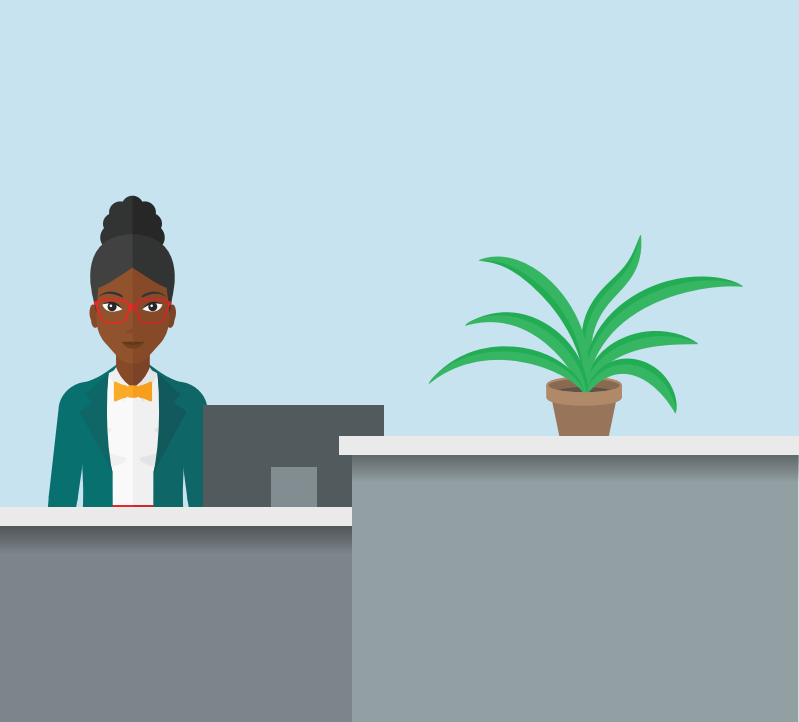 A woman who is a receptionist sits at a desk with a computer and a plant.
