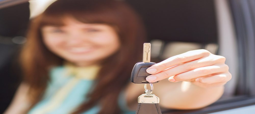 A woman sitting in the car holding out the car key