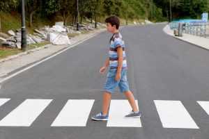 A young boy walking on the road by himself.