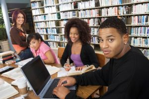 A group of college students studying together in the library.