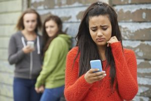 There is a young girl in the forefront. She is looking sad and holding a phone. There are two girls behind her with a phone looking at her.