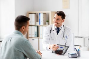 Doctor talking with patient. He is showing him something on the tablet.