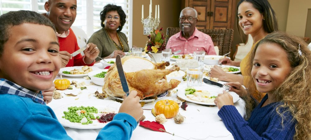 A family is sitting at a table. They are smiling as they eat their dinner.