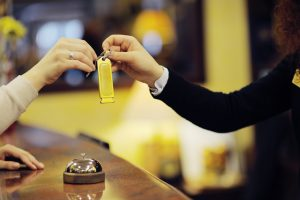A woman handing a guest her hotel keys.
