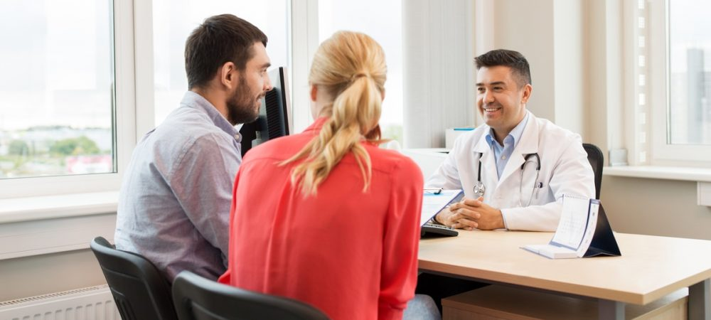 A young man and woman are meeting with a doctor