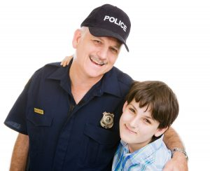 Police Officer with a boy. They are both smiling.