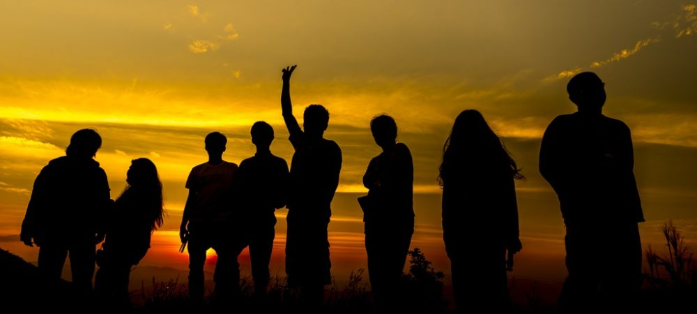 Group of peoples' silhouettes standing in front of a sunset.