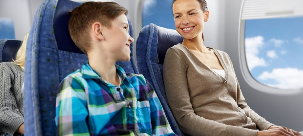 A smiling young boy and woman travelling on an airplane.