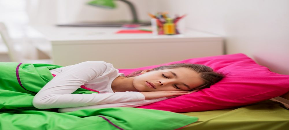 A girl asleep in her bed. There is a pink pillow and green blanket