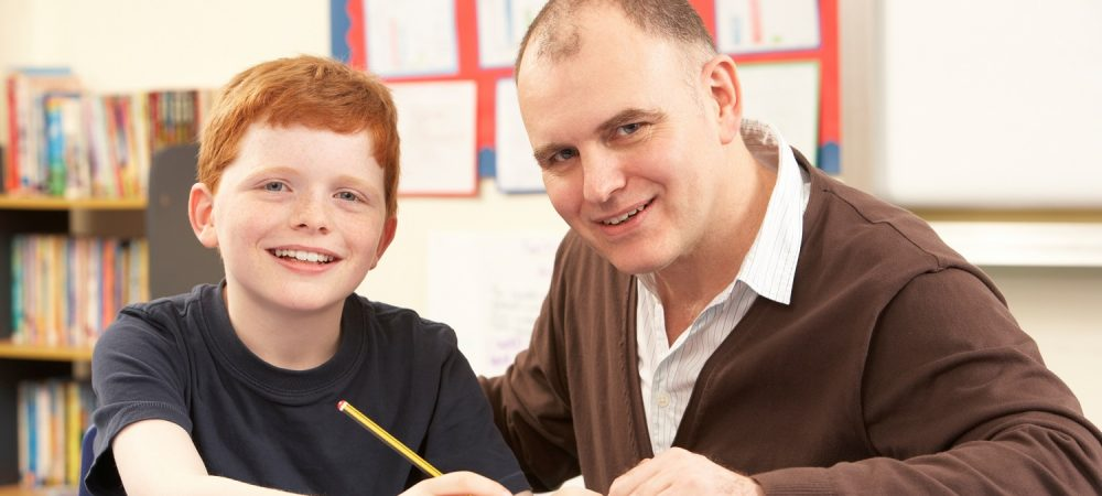 A student doing homework with his teacher.