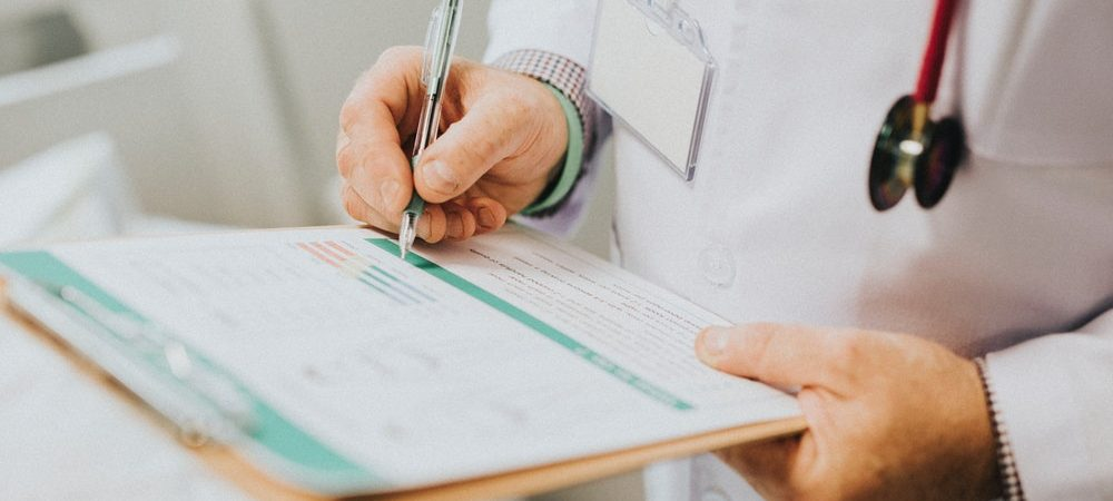A doctor holds a clipboard and writes a medical report.