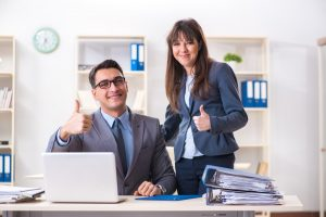 A working man and woman are by a computer giving a thumbs up