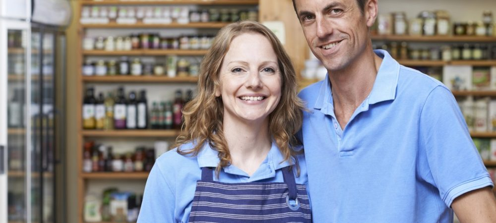A man and a woman stand together smiling in a store. The woman is wearing an employee apron for her job