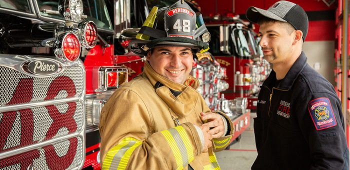 A young man wears a firefighter's uniform and gives the camera a thumbs-up as a firefighter looks on, smiling.