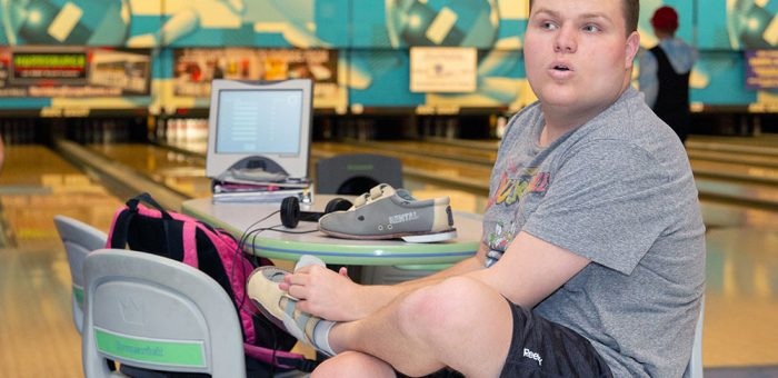 A young man puts on bowling shoes at a bowling alley.
