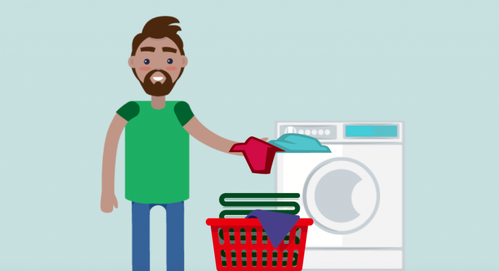 A man is shown standing next to a laundry basket, taking his laundry out of the dryer.