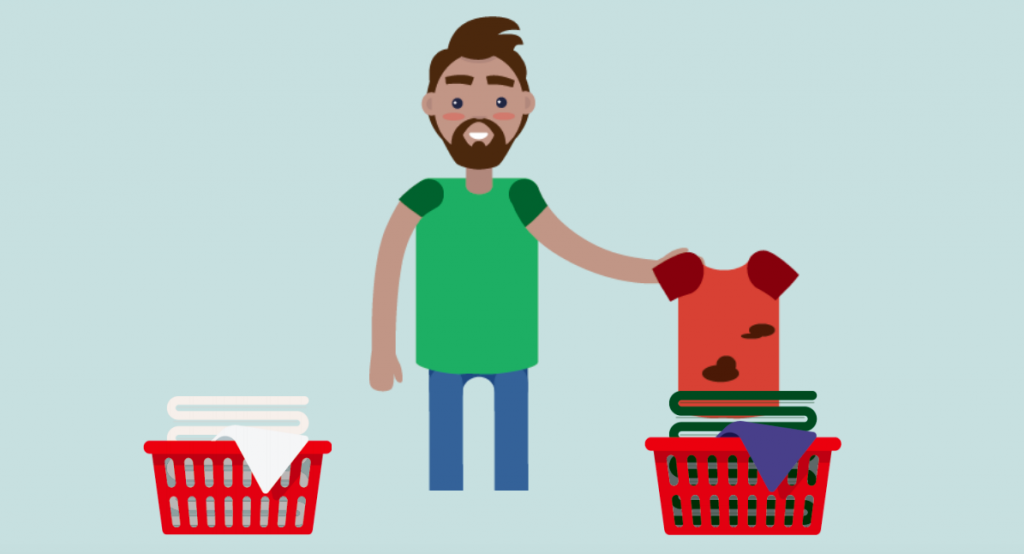 A man stands in the middle of two laundry baskets, holding a dirty shirt over the basket on the right.