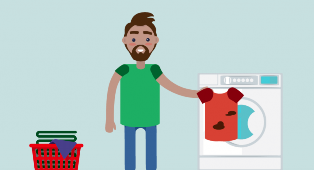A man holds a dirty shirt in front of a washing machine.