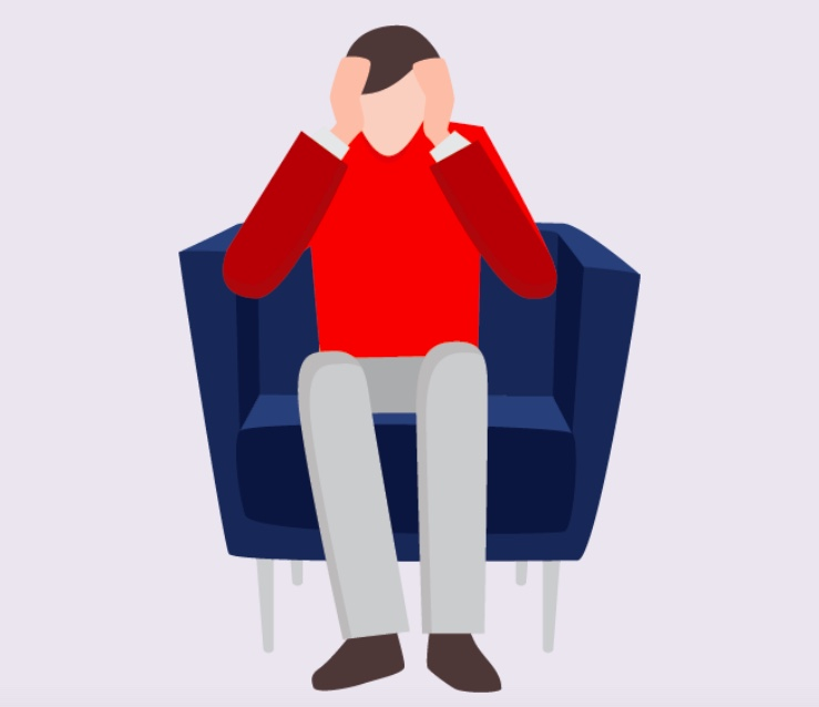 A man sitting in a chair with his hands on his head.
