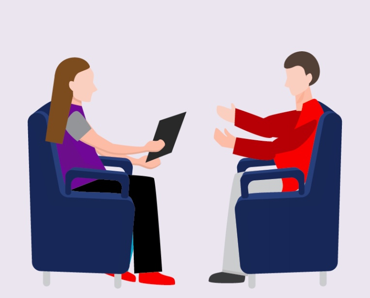 A man sitting in a chair talking to a woman sitting with a laptop.